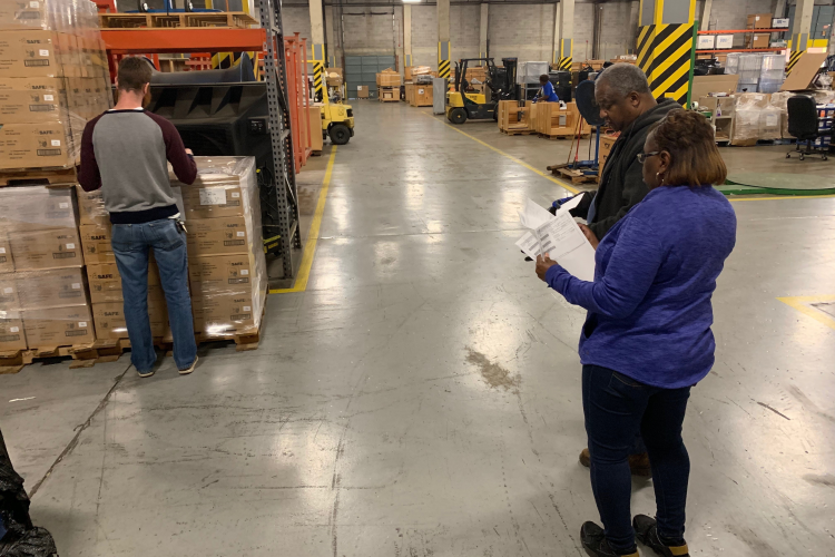 Deborah Jackson (right), a project manager for the Defense Security Cooperation Agency at Albany, Georgia, and her colleagues Robert Brantley (center), a material expeditor, and Jeremy Sexton, a project supervisor, begin to inventory, prepare, and palletize the 154,000 N95 masks to prepare them for shipment.